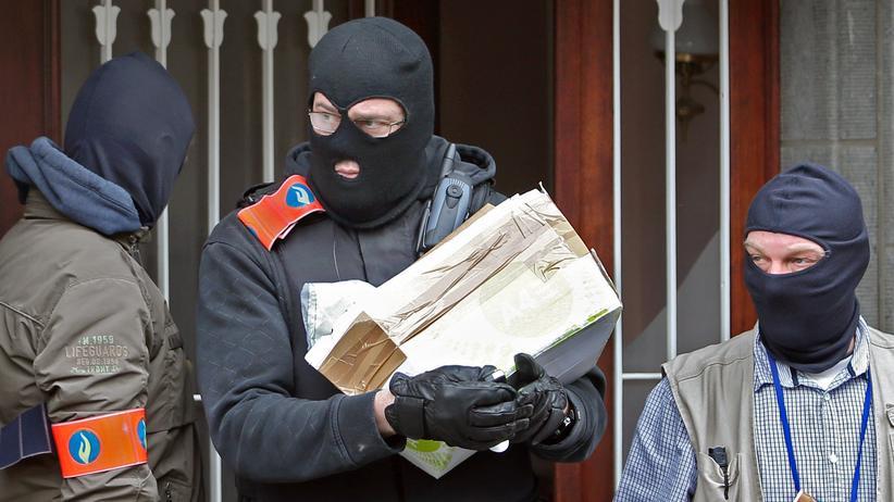 Attentäter von Brüssel : Razzia nach den Anschlägen: Belgische Polizisten bringen ein Päckchen aus einem Gebäude in Anderlecht.