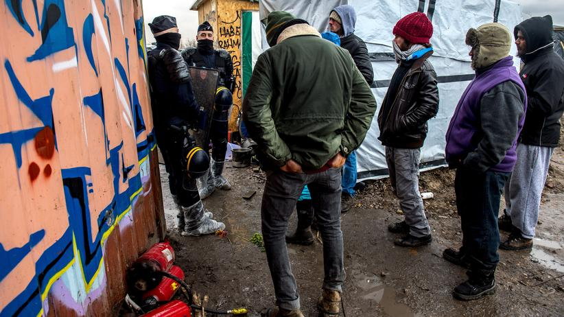 """Brexit: Anti-riot policemen block migrants as agents dismantle shelters on March 3, 2016 in the """"jungle"""" migrants and refugees camp in Calais, northern France. Demolition workers raze makeshift shelters in the southern part of the so-called Jungle migrant camp for a third day running under the close watch of dozens of police officers equipped with water cannon. / AFP / PHILIPPE HUGUEN (Photo credit should read PHILIPPE HUGUEN/AFP/Getty Images)"""