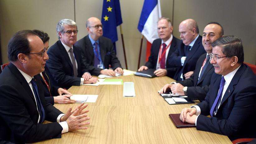 Der französische Präsident François Hollande (l.) am Tisch mit dem türkischen Ministerpräsidenten Ahmet Davutoğlu (r.) in Brüssel (18.3.2016)