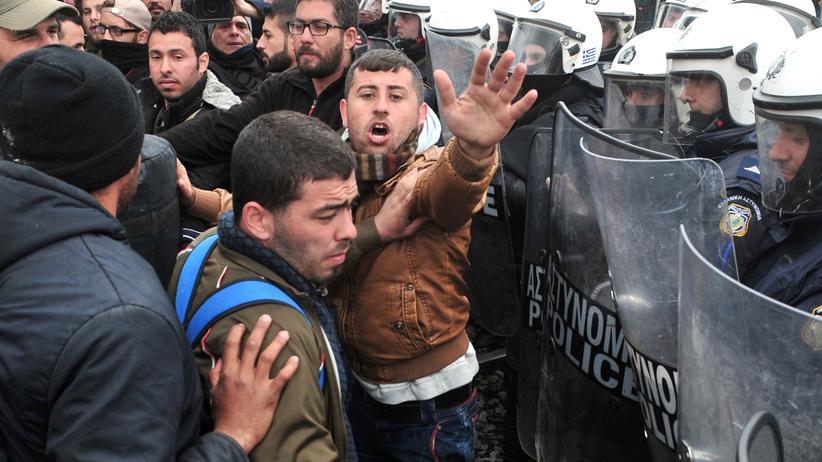 Griechische Polizisten halten Flüchtlinge von der griechisch-mazedonischen Grenze fern.