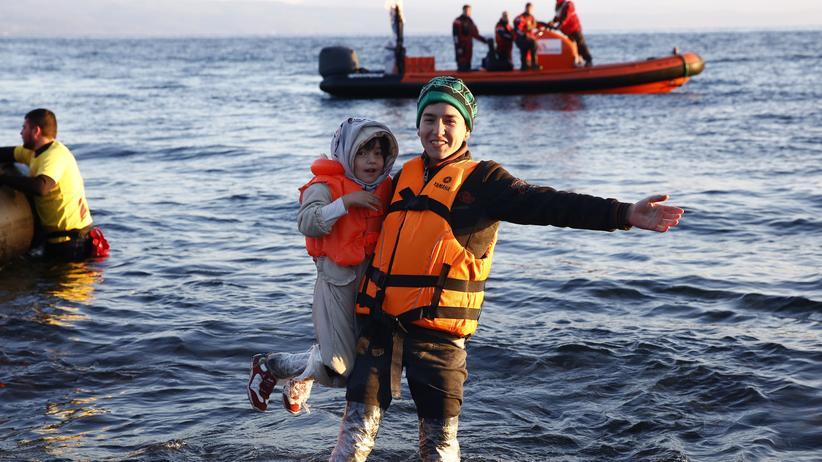 Ein afghanischer Flüchtling freut sich mit einem Kind über die glückliche Landung auf Lesbos.