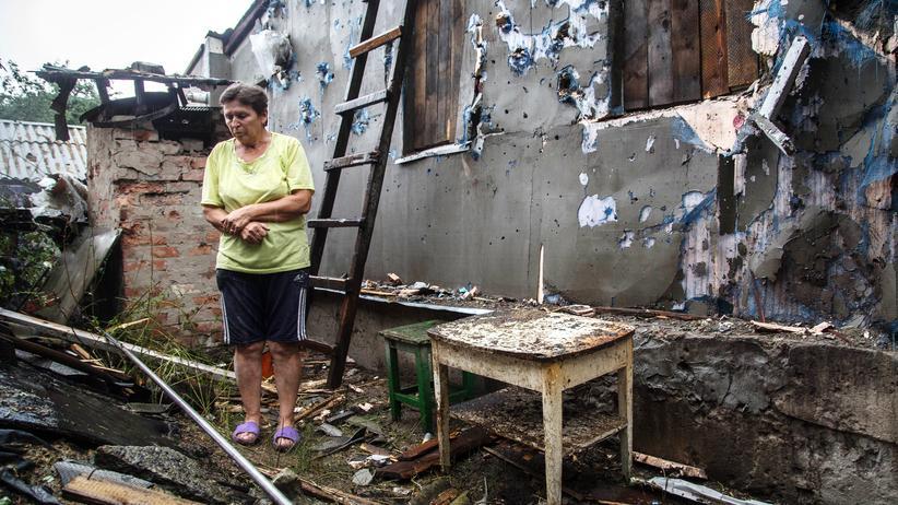 Eine Frau vor ihrem zerstörten Haus in Zolote