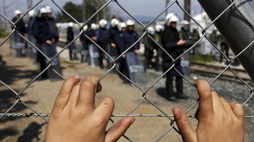 Pro Asyl: Die Hände eines Flüchtlingskindes an einem Zaun in Idomeni. Dahinter griechische Bereitschaftspolizisten, die gegen Ausschreitungen in dem selbsterrichteten Lager vorgehen.