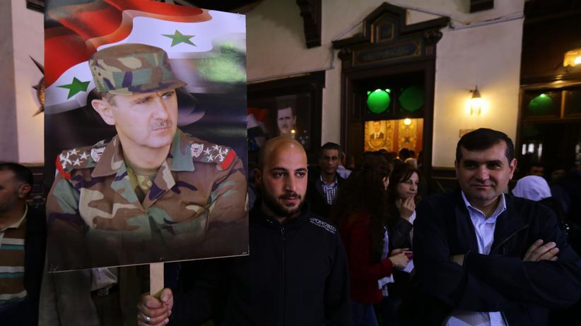 Syrien: Ein Unterstützer der Baath-Partei vor einem Wahllokal in Damaskus mit einem Plakat, das den syrischen Präsident Baschar al-Assad zeigt. (Bild vom 13. April)