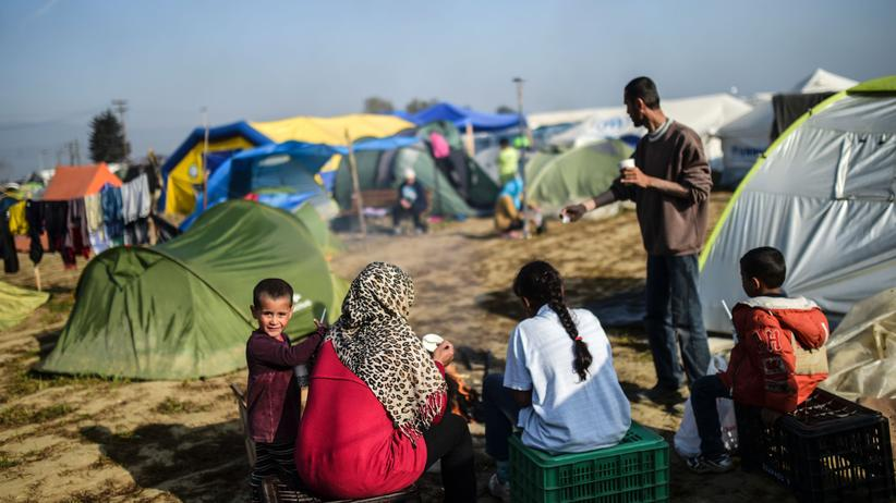 Migranten sitzen im Flüchtlingslager in Idomeni zusammen.