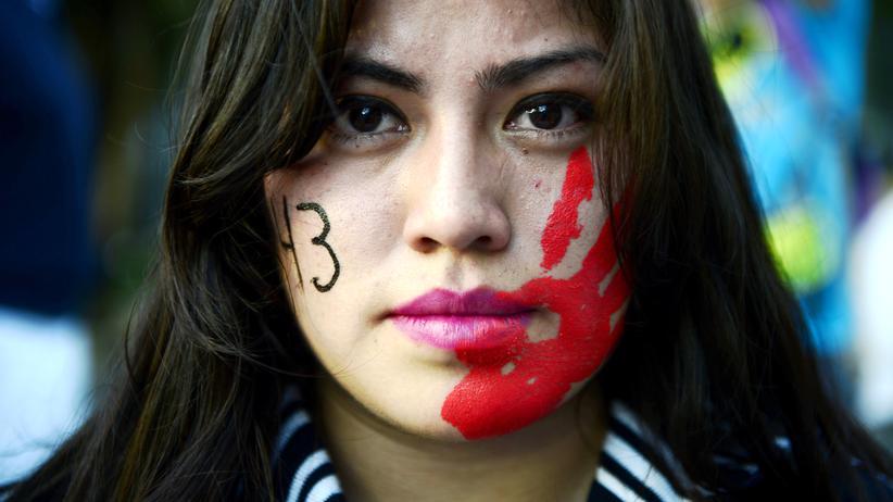 """Mexiko: """"Uns fehlen 43"""" hat diese Demonstrantin in Mexiko-Stadt auf die Fahne geschrieben."""