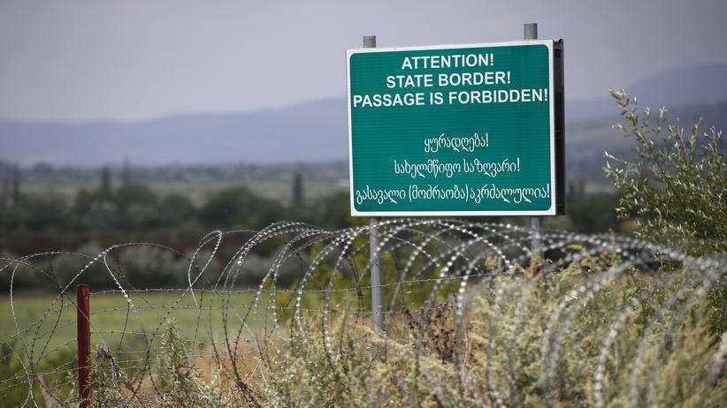 Georgien: Ein von Russland errichtetes Warnschild in Englisch und Georgisch an der Grenze zwischen der abtrünnigen Region Südossetien und Georgien (2015): Hier markiert Stacheldraht die Grenzlinie.