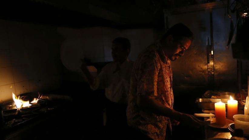Venezuela: Während eines Stromausfalls in Caracas arbeiten diese Restaurantköche im Kerzenschein weiter.