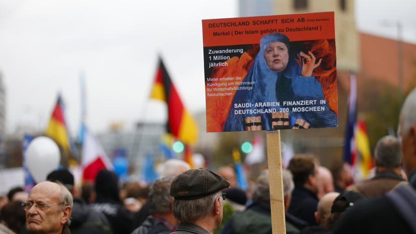 Arabische Presseschau: AfD-Demonstranten mit einem Transparent, das Kanzlerin Merkel mit Kopftuch zeigt