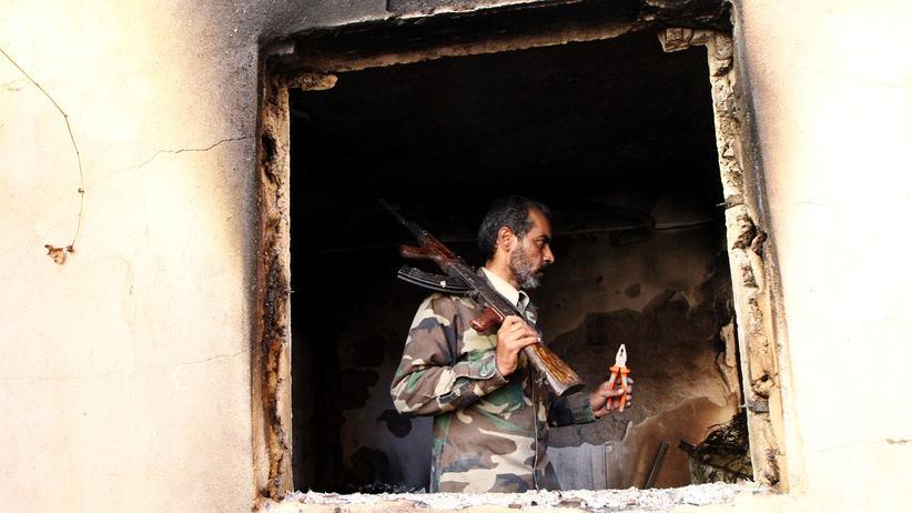 Human Rights Watch: Ein libyscher Soldat kontrolliert ein zerstörtes Haus in Bengasi.