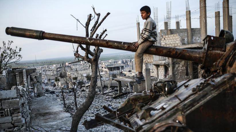 Sykes-Picot-Abkommen: Kurdischer Junge auf einem zerstörten Panzer in der syrischen Stadt Kobane (Ain al-Arab) im März 2015