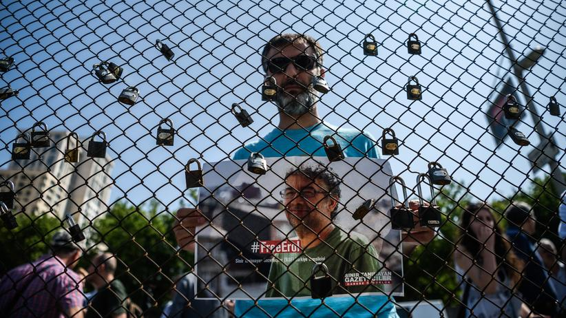Erol Önderoğlu: Ein Mann zeigt während einer Demonstration in Istanbul ein Plakat mit Erol Önderoğlu.