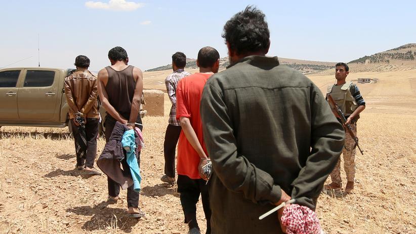 Mutmaßliche IS-Kämpfer in Syrien werden abgeführt.