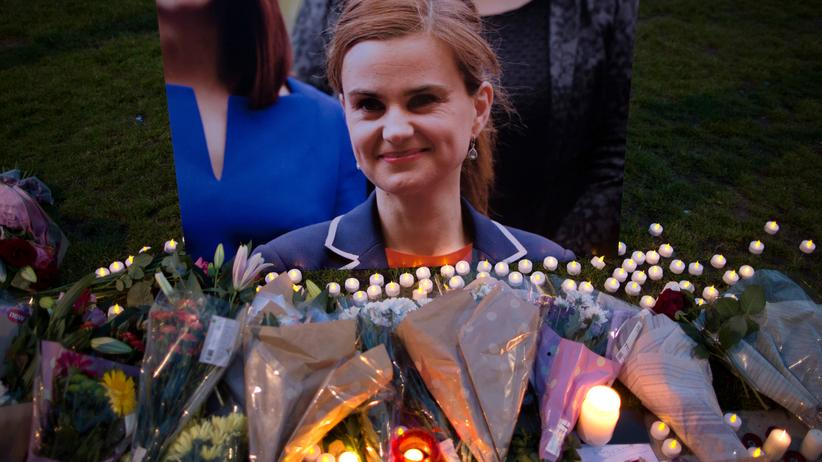 Großbritannien: LONDON, UNITED KINGDOM - JUNE 16: Flowers surround a picture of Jo Cox during a vigil in Parliament Square on June 16, 2016 in London, United Kingdom. Jo Cox, 41, Labour MP for Batley and Spen, was shot and stabbed by an attacker at her constituicency today in Birstall, England. A man also suffered slight injuries during the attack. Jo Cox was reportedly shot and stabbed while holding her weekly surgery at Birstall Library, Birstall near Leeds and later died. A 52-year old man has been arrested in connection with the crime. (Photo by Dan Kitwood/Getty Images)