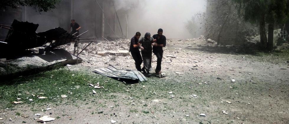 Menschen fliehen vor einer Staubwolke, nachdem ein Gebäude in Damaskus eingestürzt ist.