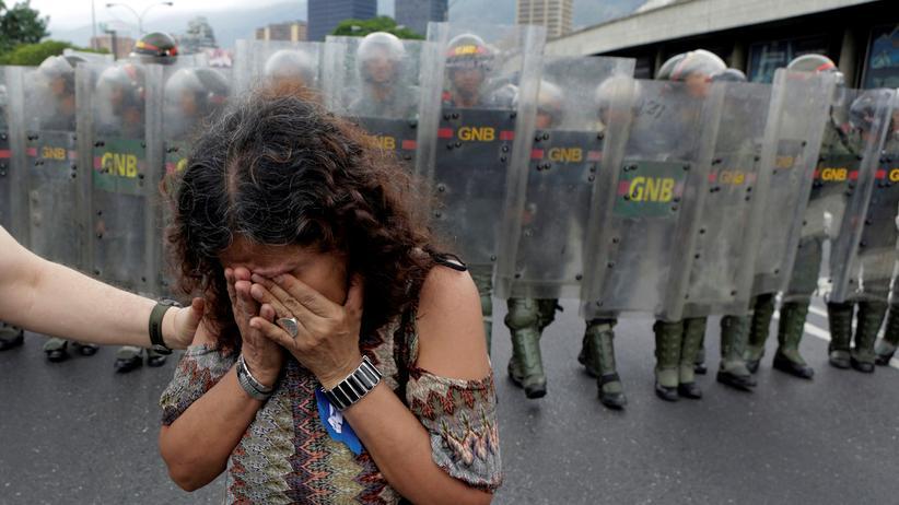 Venezuela: Bei einer Demonstration gegen den venezolanischen Präsidenten Nicolás Maduro in Caracas geht eine Anhängerin der Opposition der Polizei aus dem Weg.