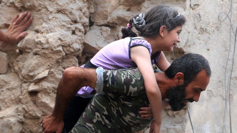 Ein Mann trägt ein Mädchen durch Trümmer