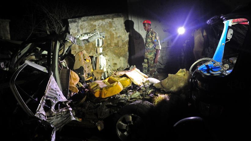 Ein Somalischer Soldat steht neben dem Autowrack, in dem die Bombe deponiert war.