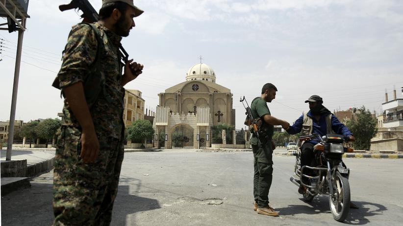 Syrien: Kurdische Milizionäre kontrollieren einen Motorradfahrer im syrischen Hassaka.