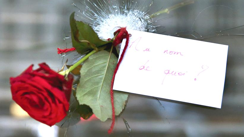"""Anschläge von Paris: Ein Restaurantfenster, einen Tag nach den Anschlägen in Paris am 13. November 2015. """"Im Namen wovon?"""" steht auf dem Schild."""
