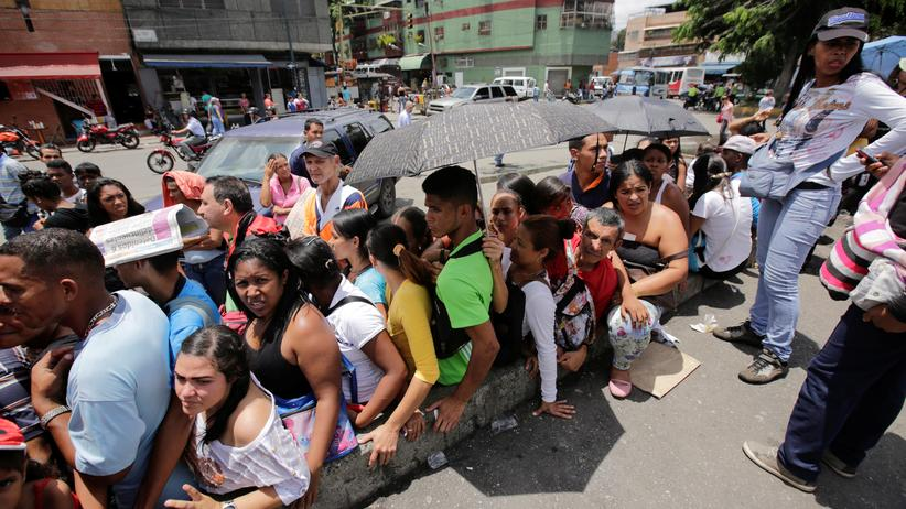 Venezuela: Menschen in Venezuelas Hauptstadt Caracas warten in einer Schlange vor dem Supermarkt.