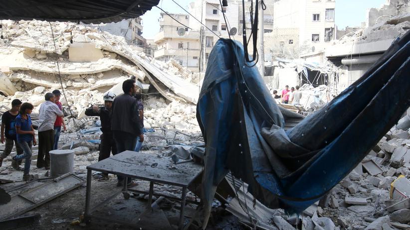 Aleppo: Bewohner in dem von den Rebellen kontrollierten Stadtteil Aleppos betrachten die Trümmer des Marktes, der am Mittwoch bombardiert wurde.