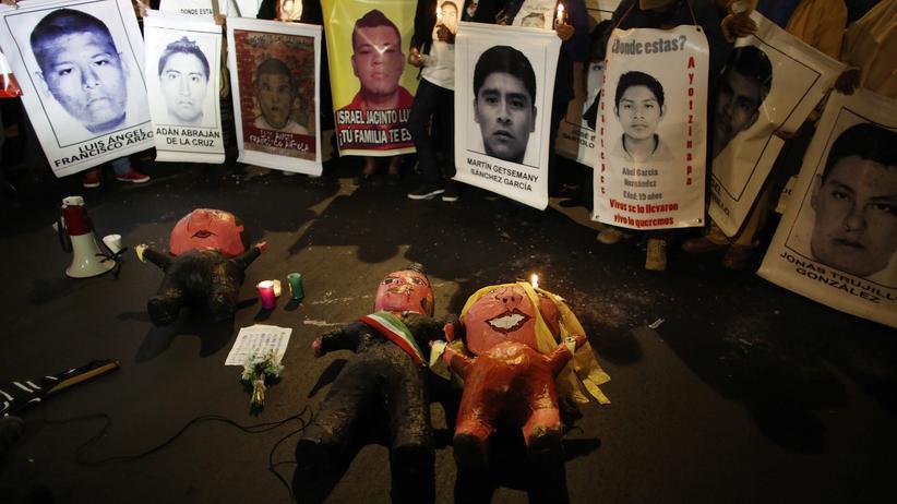 Mexiko: Angehörige halten Porträts der 43 verschwundenen Lehramtsstudenten vor Figuren von Mexikos Präsident Peña Nieto (Mitte), seiner Frau Angelica Rivera (rechts) und Generalstaatsanwalt Jesús Murillo Karam. Die Familien werfen den ihnen vor, die wahren Täter zu schützen.