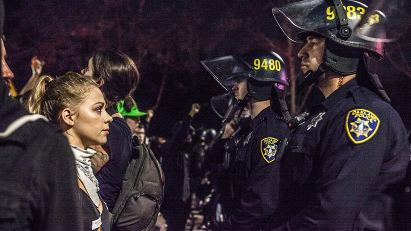 Donald Trump: Eine junge Frau schaut einem Polizisten, der ihr am 10. November in Oakland den Weg versperrt, tief in die Augen.