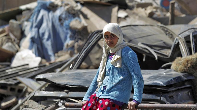 Jemen: Ein Mädchen sitzt im Jemen vor einem zerstörten Haus, das bei einem Luftangriff der von Saudi-Arabien geführten Militärkoalition zerstört wurde.