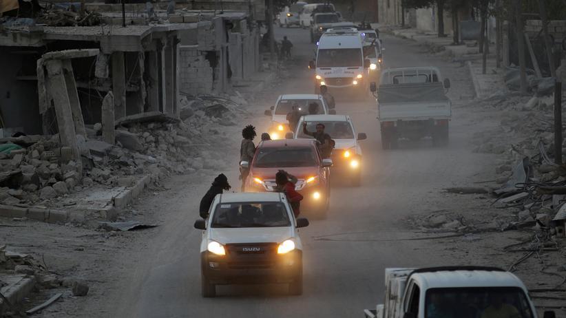 Rebellen fahren durch das zerbombte Aleppo.