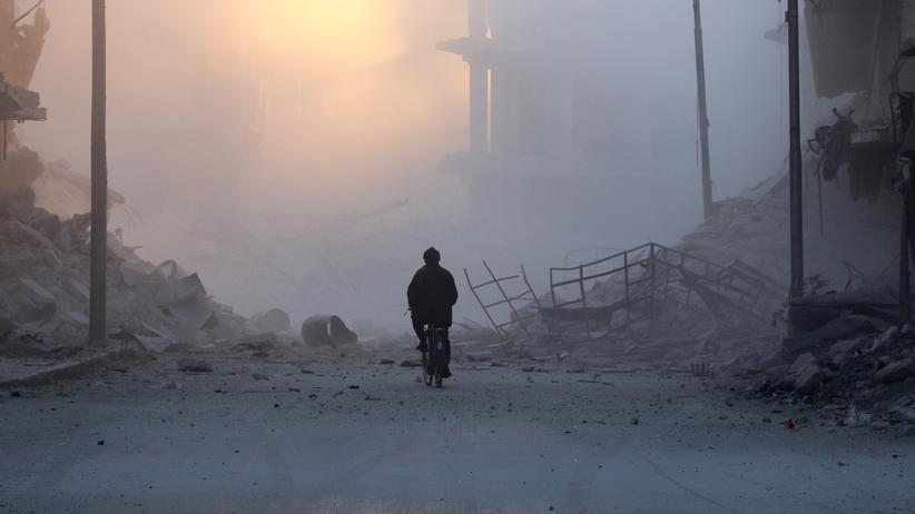 Syrien: Nach einem Luftangriff auf die Rebellengebiete in Aleppo radelt ein Mann am 26. November durch die Trümmer.