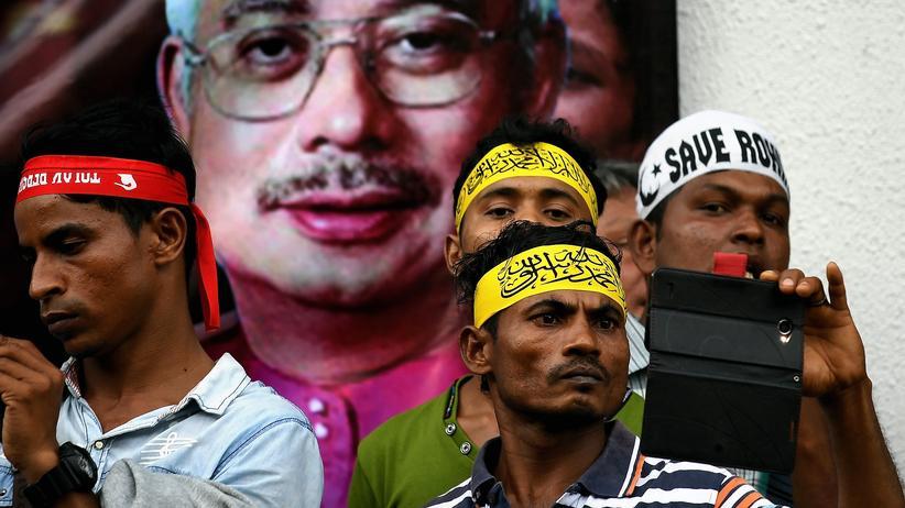 Rohingya: Muslimische Rohingya-Flüchtlinge bei einer Solidaritätskundgebung in Kuala Lumpur vor einem Bild des malaysischen Ministerpräsidenten Najib Razak.