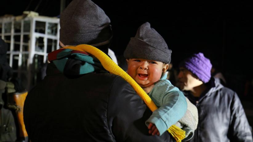 Ein Mann träg ein Kind, das aus Aleppo evakuiert wurde