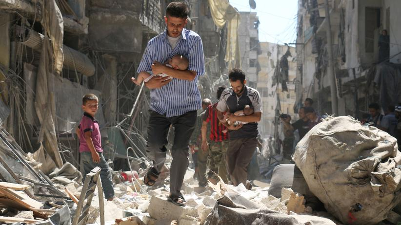 Syrien: Männer retten im September kleine Kinder aus den Trümmern eines Hauses nach einem Bombenangriff auf einen damals noch von Rebellen gehaltenen Teil von Aleppo.