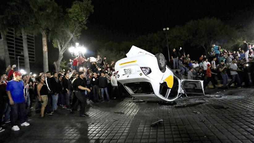 Demonstranten in Mexiko haben ein Auto umgeworfen.