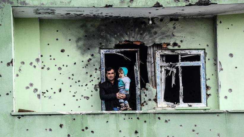 UN-Bericht: Ein Kurde steht mit einem Kind auf dem Balkon eines zerstörten Hauses in Silopi.