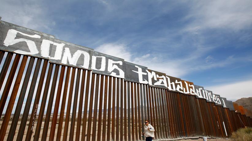 """USA: Mexikanische Aktivisten haben """"Wir sind Arbeitskräfte"""" auf den Grenzzaun zu den USA geschrieben."""