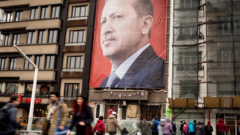 Deutschtürken: Passanten auf dem Taksim-Platz in Istanbul laufen an einem Porträt des türkischen Präsidenten Recep Tayyip Erdoğan vorbei.