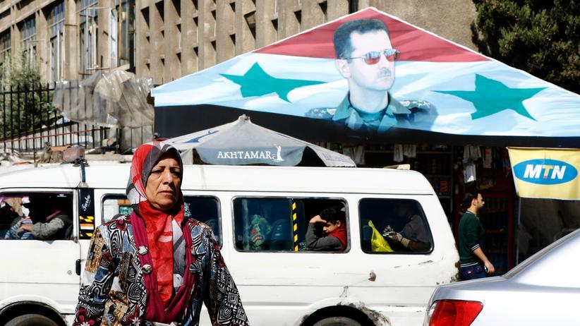 Baschar al-Assad: Eine Frau vor einem Porträt des syrischen Machthabers Baschar al-Assad.