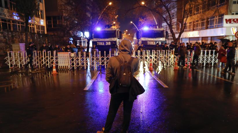 Ein Demonstrant blickt auf Polizisten in Ankara.