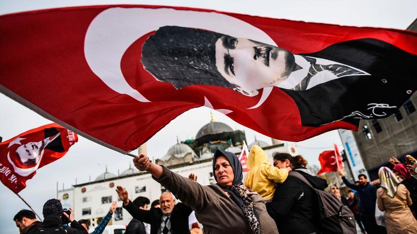 Verfassungsreform in der Türkei: Eine Gegnerin der Verfassungsänderung schwenkt in Istanbul eine Fahne mit dem Bild von Staatsgründer Mustafa Kemal Atatürk. Hinter ihr stehen Befürworter der Reform. Wer gewinnt, entscheidet sich am 16. April.