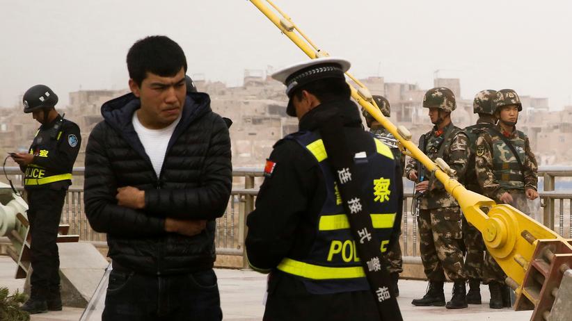 Unruheprovinz Xinjiang: Ein Polizist kontrolliert in der Stadt Kaschgar in der Provinz Xinjiang die Papiere eines Uiguren.