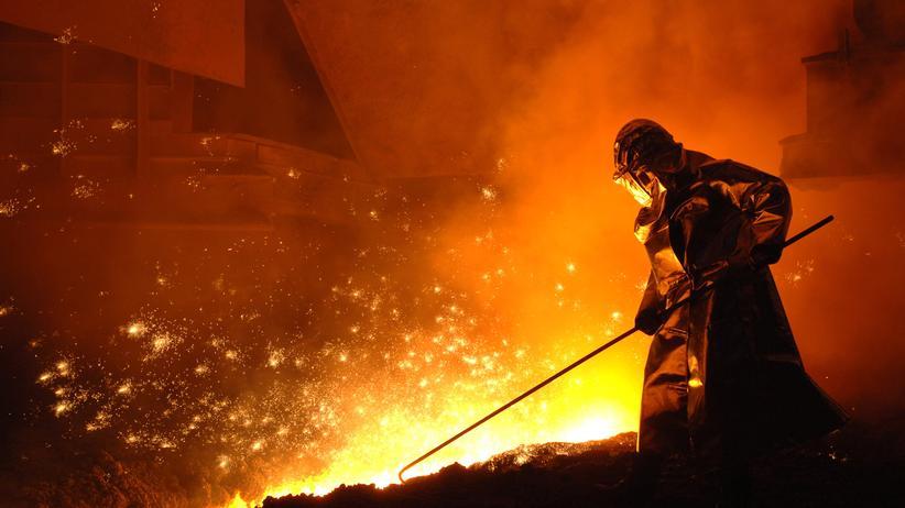 USA: Ein Stahlwerker arbeitet während des Abstiches am Hochofen im brandenburgischen Eisenhuettenstadt.