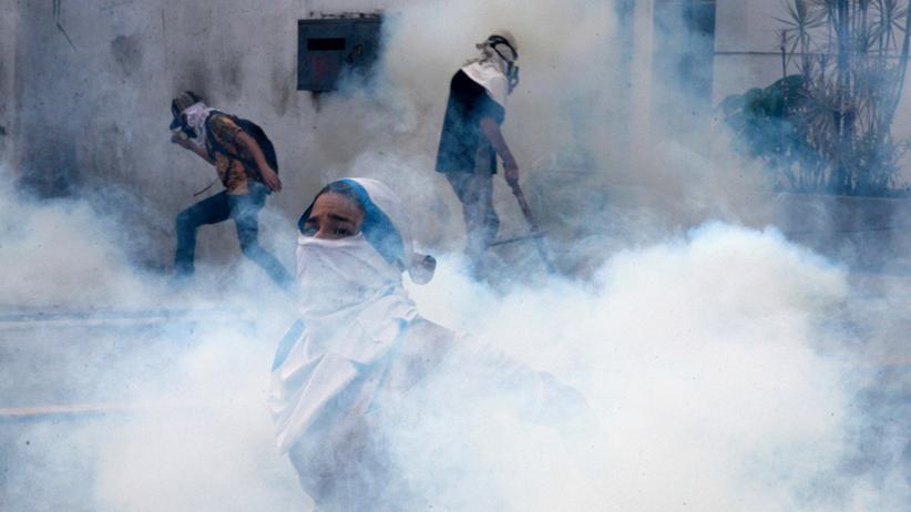 Venezuela: Demonstranten in Caracas bringen sich vor Tränengas in Sicherheit.