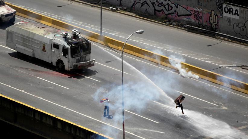 Venezuela: Ein Demonstrant wird in Caracas von einem Wasserwerfer getroffen.