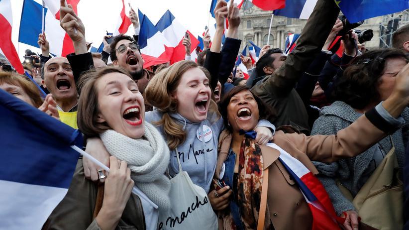Reaktionen zur Präsidentenwahl: Macron-Unterstützer freuen sich über das Wahlergebnis am Louve Museum in Paris, Frankreich.