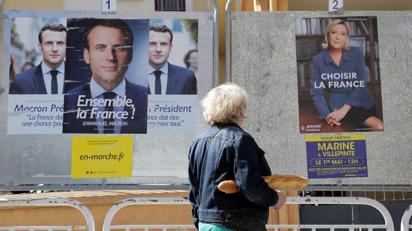 Präsidentschaftswahl in Frankreich: Eine Frau steht von Wahlplakaten der französischen Präsidentschaftskandidaten.