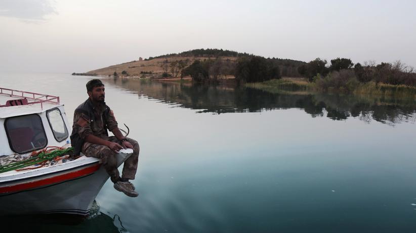 Syrien: Ein Kämpfer der SDF-Rebellen auf einem Boot, das auf dem See vor dem eroberten Staudamm in Tabka treibt