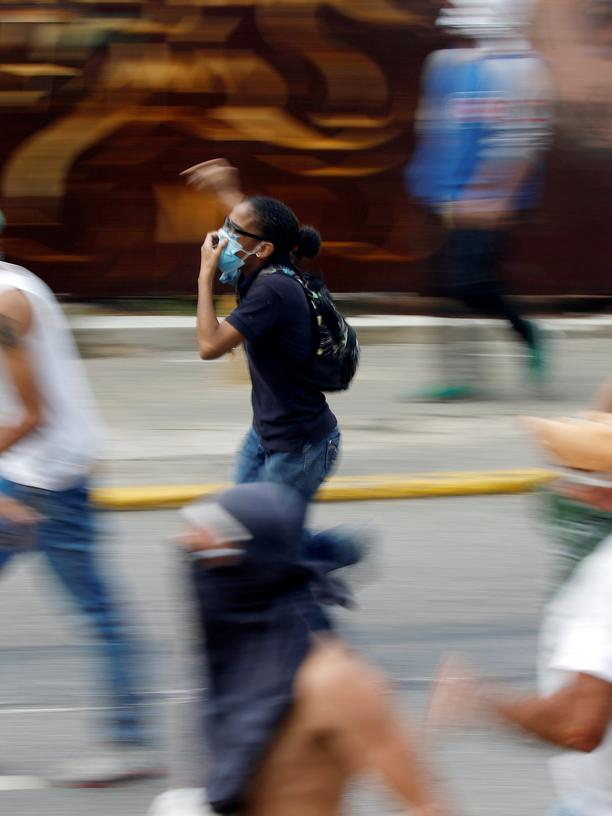 "Venezuela: Opposition demonstrators run away while clashing with riot police during the so called ""mother of all marches"" against Venezuela's President Nicolas Maduro in Caracas, Venezuela, April 19, 2017. REUTERS/Carlos Garcia Rawlins - RTS1314E"