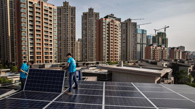 Chinesische Arbeiter installieren in Wuhan eine Solarstromanlage.